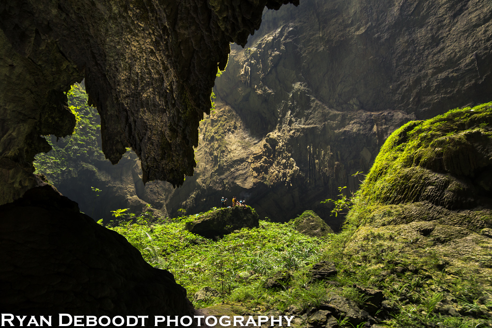 Several people standing at the top of the first doline (hole in the roof), Hang Son Doong.